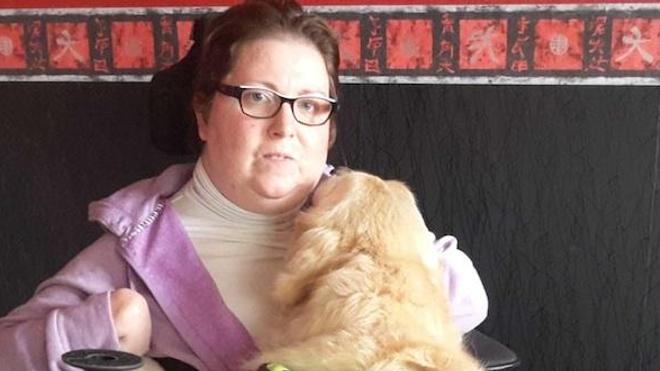 Laurence Lemaître sur son fauteuil roulant, accompagnée de son chien d'assistance