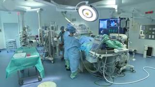 Le chirurgien suit sa progression jusqu'au coeur sur un écran radioscopique.