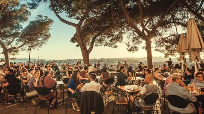 Personnes rassemblées en terrasse à Lisbonne, Portugal, où le nombre de cas de covid repart à la hausse.